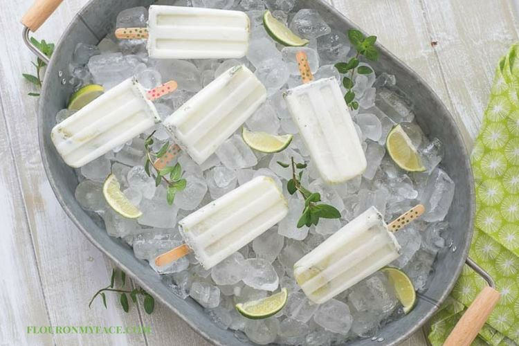 How to serve cocktail popsicles at your next party. Coconut Mojito Ice Pops served in a galvanized steel serving tray on a bed of ice.
