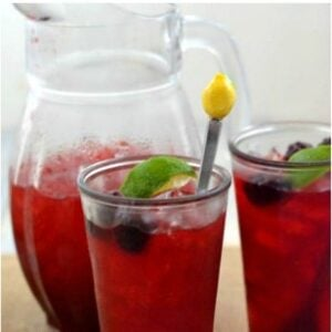 Blackberry Iced Cooler in glass with a pitcher beside.