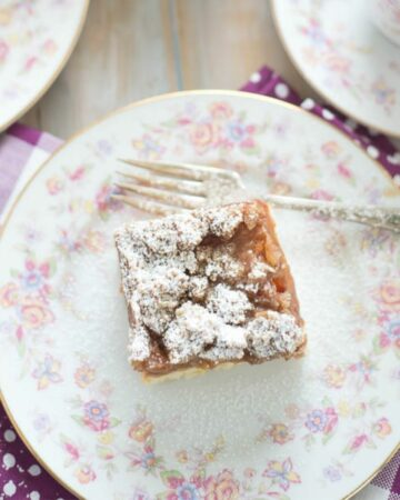 A square piece of apple stuesel crumb cake on a dessert plate.