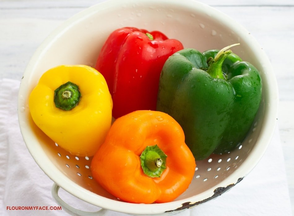 Fresh whole yellow, red, green and orange bell peppers in a white enamel colander