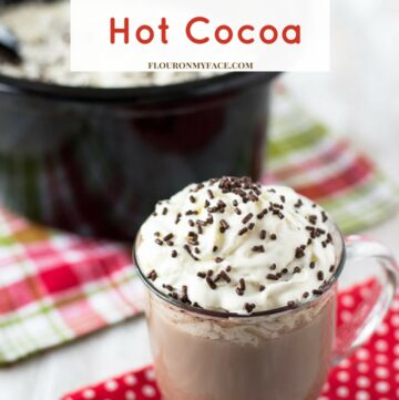 Coffee mug filled with Crock Pot Hot Cocoa topped with whipped cream and brown sprinkles.