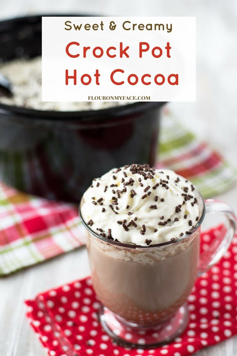 Coffee mug filled with a Crock Pot Hot Cocoa recipe topped with whipped cream and brown sprinkles.