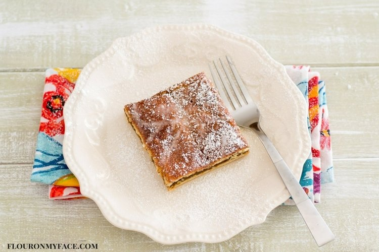 A square serving piece of Pumpkin Butter Crescent Bars on a white plate.