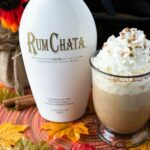 Pumpkin RumChata Latte served in a big clear mug, topped with whipped cream, ground cinnamon and garnished with a cinnamon stick.