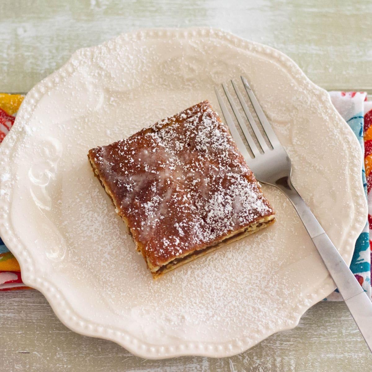 A square piece of pumpkin butter crescent bars on a dessert plate.