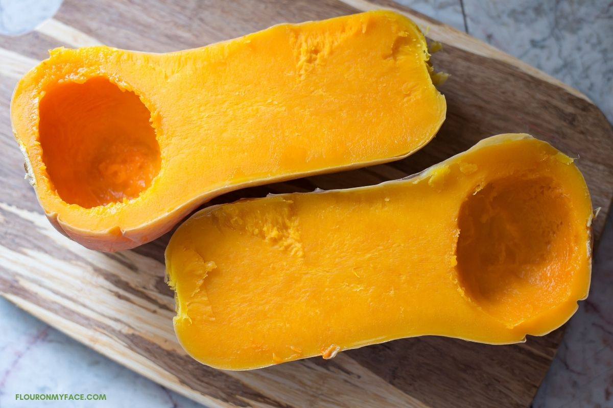unpeeled and cooked butternut squash cut in half with the seeds cleaned out on a wooden cutting board
