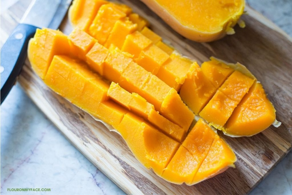cutting cooked butternut squash into cubes on a wooden cutting board