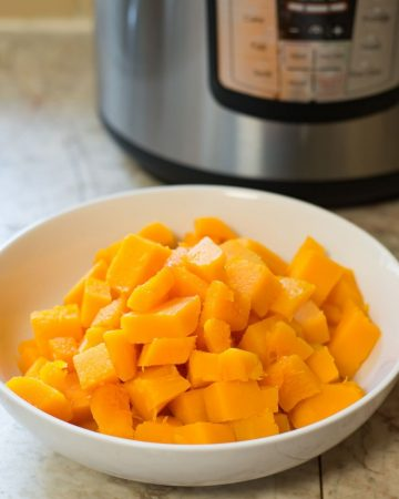 Cubed Butternut Squash in a bowl with the Instant Pot appliance in the background