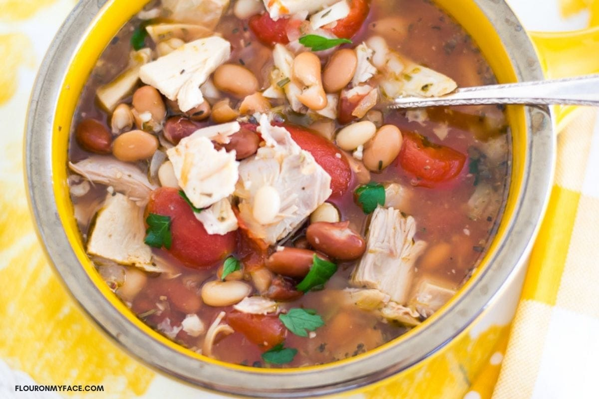 Overhead photo of Turkey and three bean soup in a yellow soup bowl.