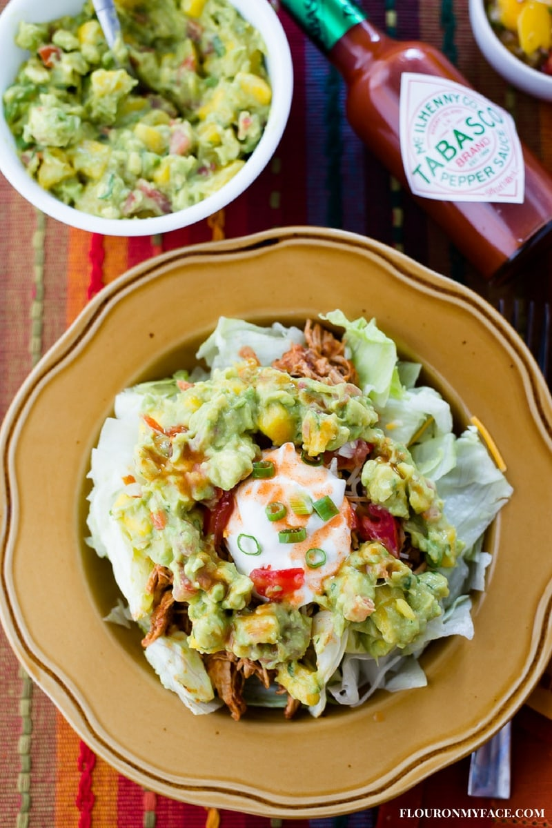 Chicken Taco Salad topped with chunky mango guacamole with sour cream and Tabasco Sauce