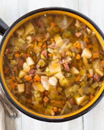 A large brown soup serving bowl filled with Ham Cabbage Potatoes Soup