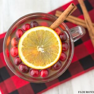 Hot Apple Cider Christmas Wassail recipe served in a mug on a black and red plaid cloth napkin with fresh cranberries, an orange slice and a cinnamon stick for garnish.