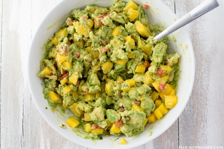 Chunky Mango Guacamole recipe in a white serving bowl with a spoon