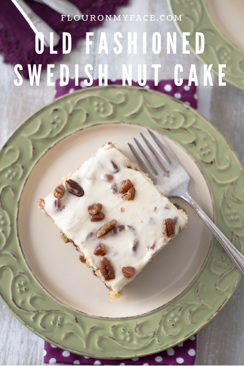 A slice of Old Fashioned Swedish Nut Cake recipe served on a green and cream dessert plate with a purple napkin and a vintage dessert fork.