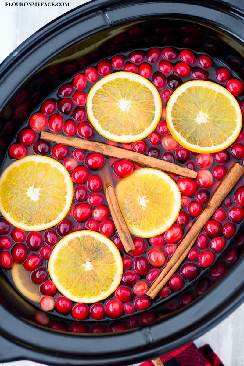Slow Cooker Apple Cider Wassail recipe served in a 6 quart slow cooker with fresh cranberries, thin orange slices and cinnamon sticks.