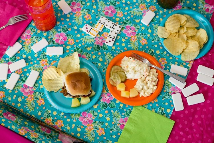Luau game night kids table ideas. Let the kid eat and play domnino's at the same game table. Luau themed tablecloth and party decorations.