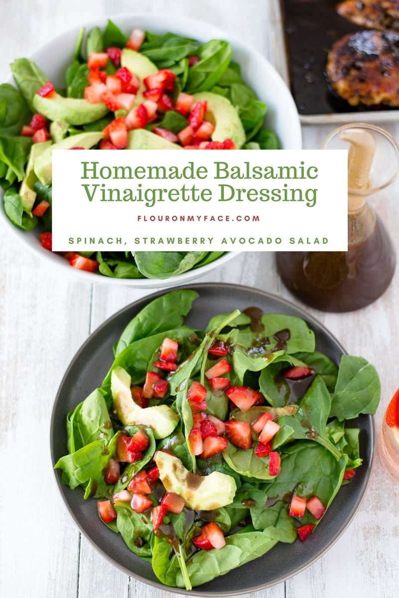 Homemade Balsamic Vinaigrette Dressing in a bottle next to a white glass serving bowl of Spinach, Strawberry and Avocado Salad