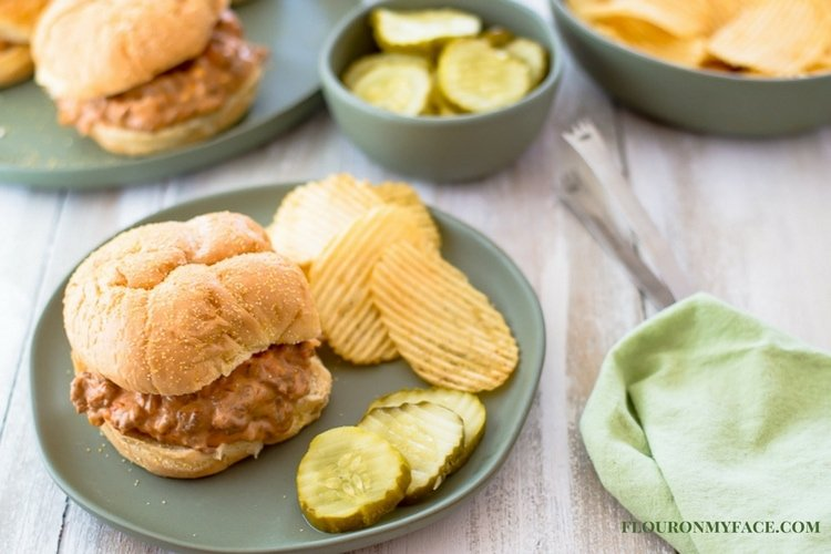 Crock Pot Cheesy Salsa Sloppy Joes recipe on a plate on the table with a green cloth napkin