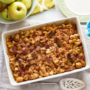 Mother's Day Apple Cinnamon Bacon Breakfast Casserole on table with plates, vintage silverware and a bowl of yellow apples