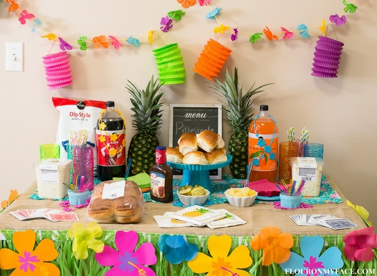 Luau Game Night Table top decorated with a grass banner and Luau themed food. Pineapple Pulled Pork Sliders and supplies from Publix