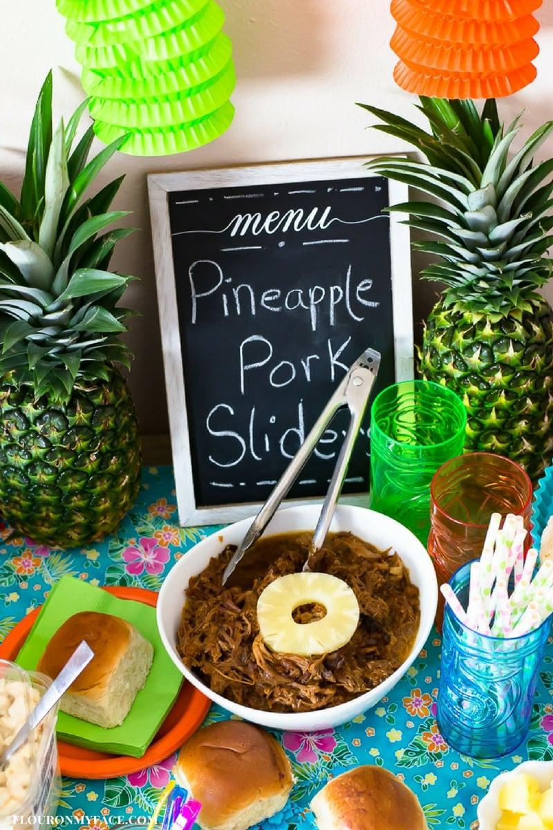 Crock Pot Pulled Pork recipe in a white serving bowl on a Luau themed party table with fresh pineapple in the background