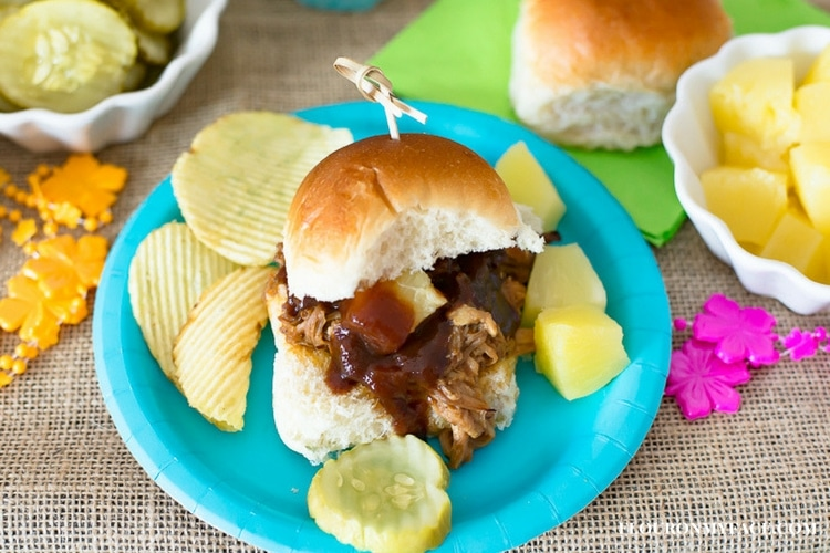 Pineapple Pork Sliders, on a blue plate served with chips, pickle slices and pineapple chunks