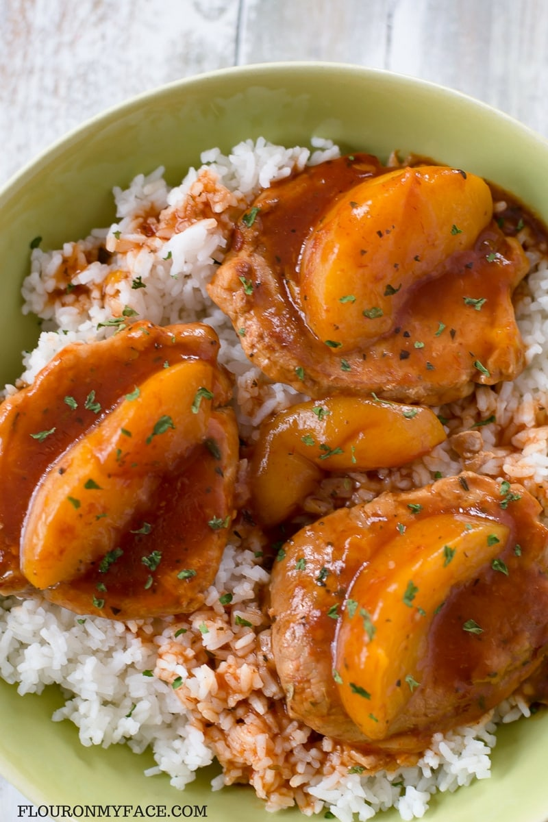 Spicy Peach Pork Chop recipe made in the crock pot and served over a bed of cooked white rice.