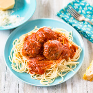 A light blue plate with a serving of cooked spaghetti noodles with 3 meatballs with spaghetti sauce on top of the pasta