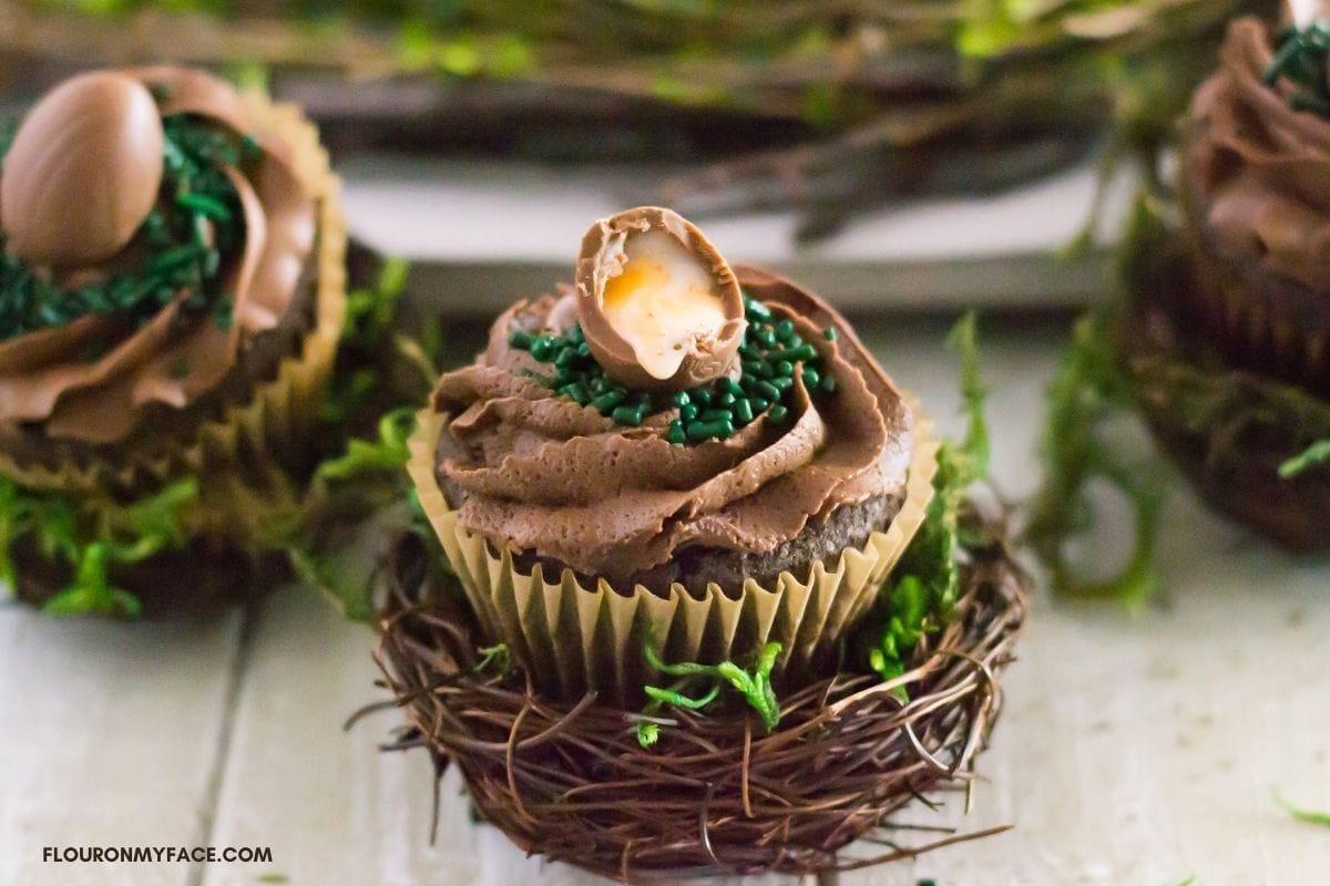 A chocolate cupcake inside a decorative nest topped with a cadbury egg.