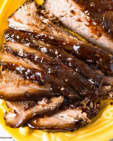 A yellow glass serving platter with a slow cooker smoked barbecue beef brisket that has been sliced for serving