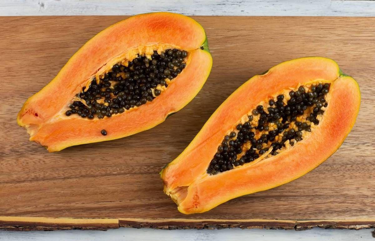 A fresh papaya cut open in half on a wooden cutting board.