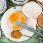Homemade Peach Rosemary Jam Recipe spread on a biscuit with a vintage butter knife.