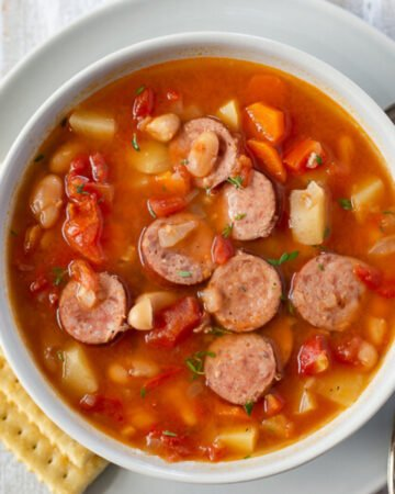 a soup bowl filled with kielbasa soup that was made in the crock pot