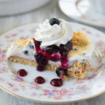 sliced no bake blueberry cheesecake pie on a floral patterned dessert dish with whipped cream and blueberry sauce drizzled over it.