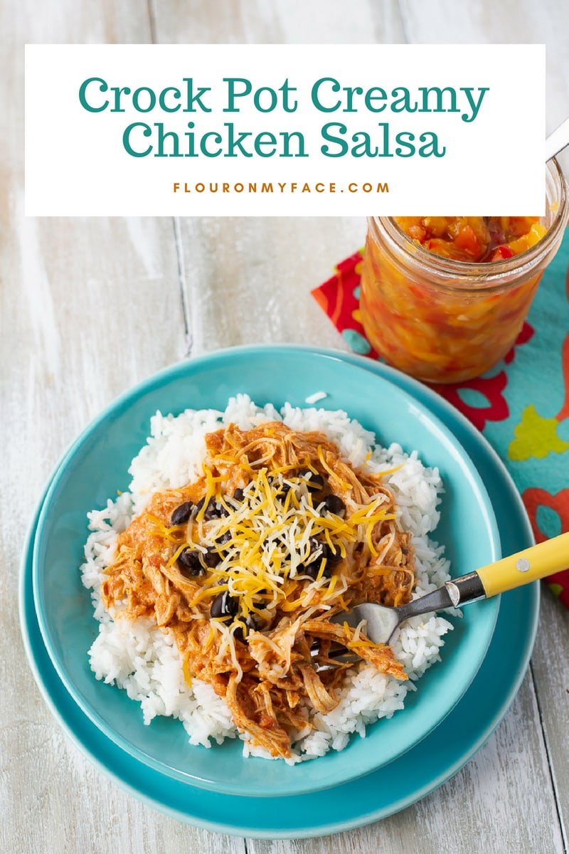 Crock Pot Creamy Chicken Salsa recipe served over white rice in a teal bowl with homemade salsa in a jar