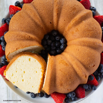 Old Fashioned Million Dollar Pound Cake recipe served on a cake plate circles with fresh strawberries and blueberries