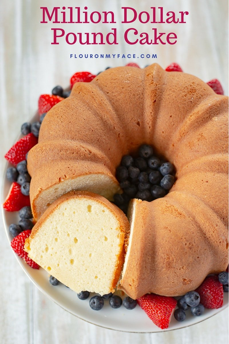 Million Dollar Pound Cake recipe served on a cake platter with fresh berries.