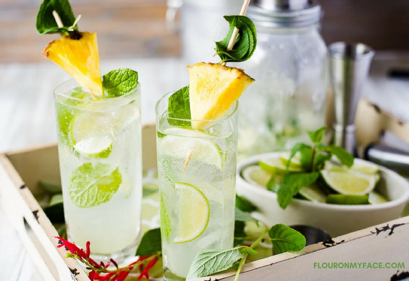 Pineapple Sage Mojito recipe in a tall glass on a serving platter with cocktail shaker and ingredients