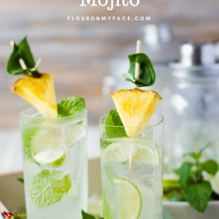Tall glasses filled with Pineapple Sage Mojito cocktail on a serving tray with fresh pineapple and fresh mint.