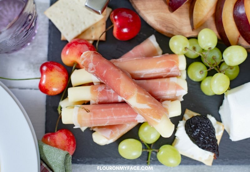 Meat and Cheese Rolls served on a slate and wooden cheese platter with fresh fruit.