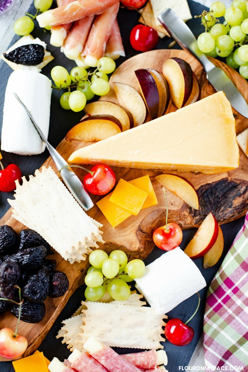 Rustic Wooden Cheese Board serving fresh summer fruit and cheese platter appetizers.