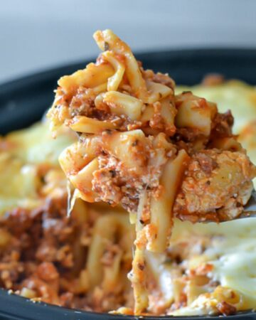 Closeup image of a serving spoon lifting crock pot baked ziti from the slow cooker.