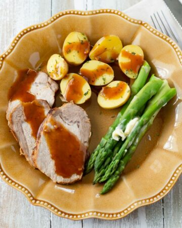 Honey garlic pork loin served on a dinner plate with potatoes and asparagus.
