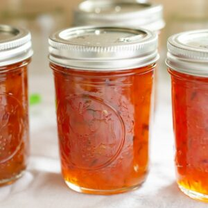 Half pint canning jars filled with Peach Lime Chutney.