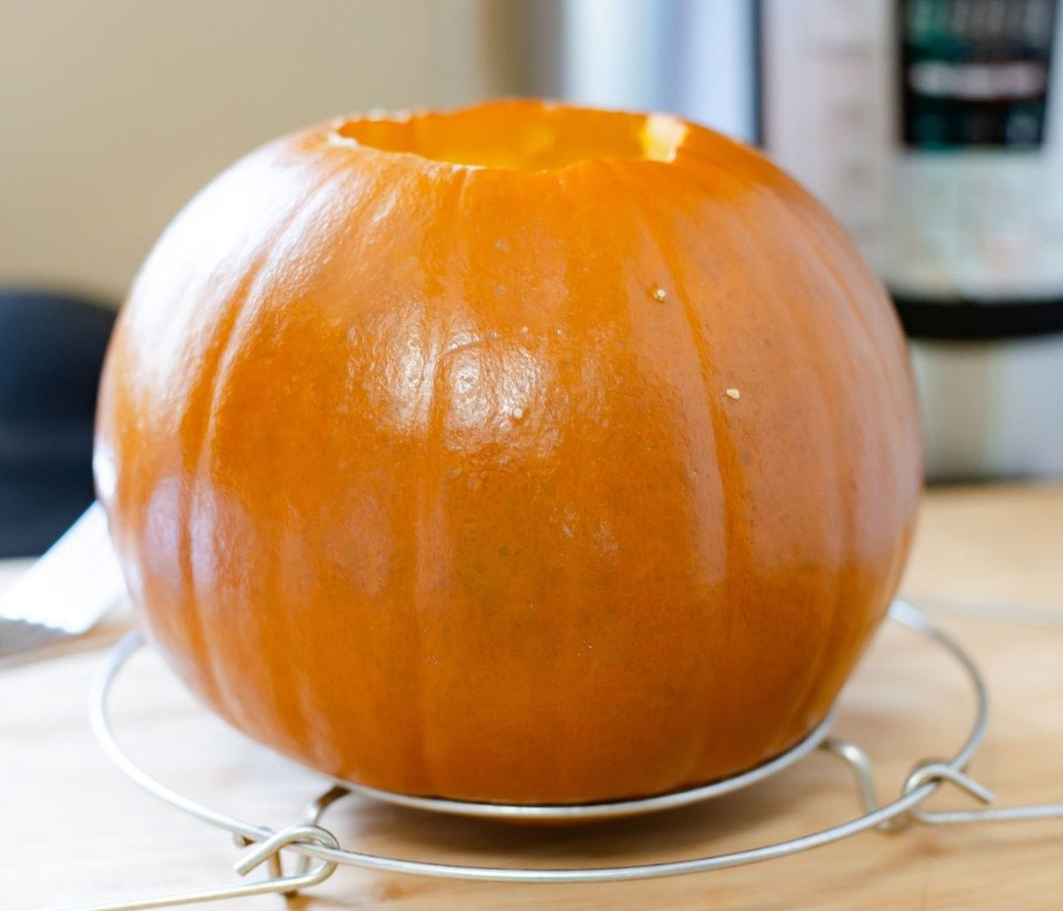A cooked pie pumpkin cooling on a metal rack.