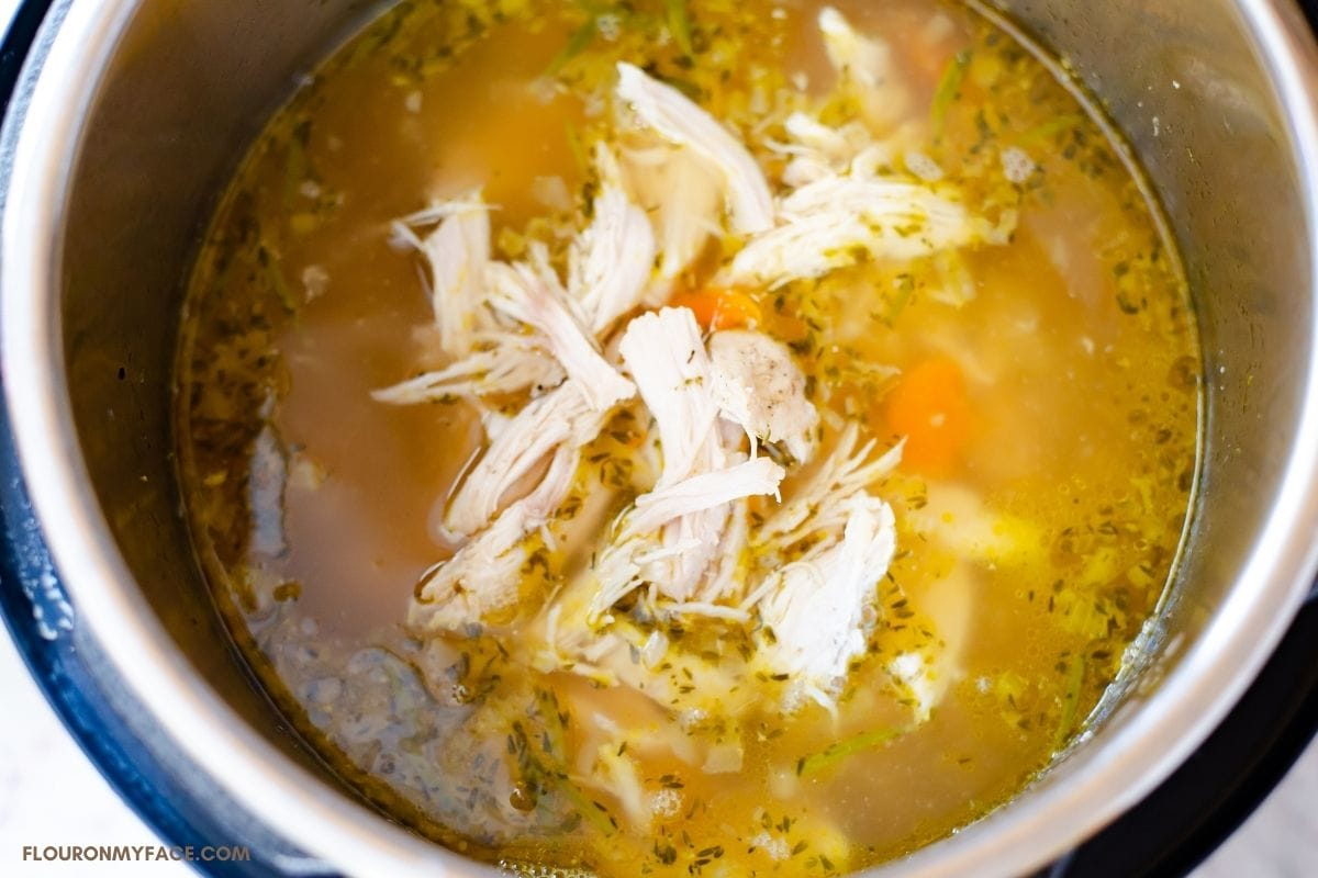 Putting cooked and shredded chicken into the pot of soup.