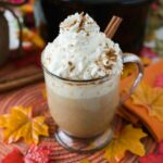 A mug filled with Pumpkin Spice Rumchata Latter on a Fall decorated tables top.