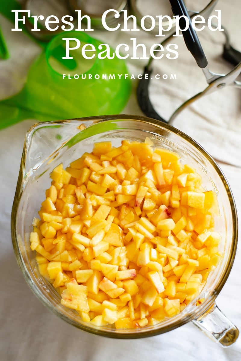A large glass measuring cup with fresh chopped peaches for marmalade recipe