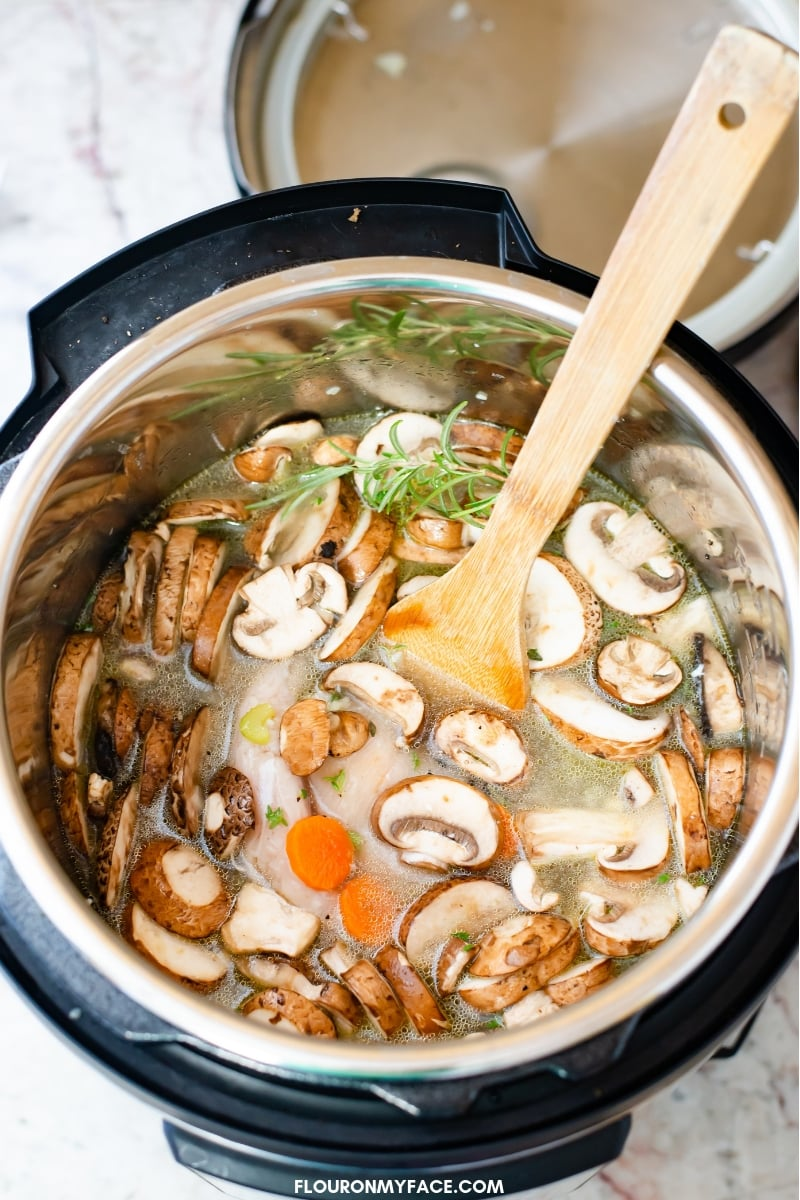 Instant Pot Chicken Wild Rice Soup recipe ingredients in the pressure cooker before cooking.