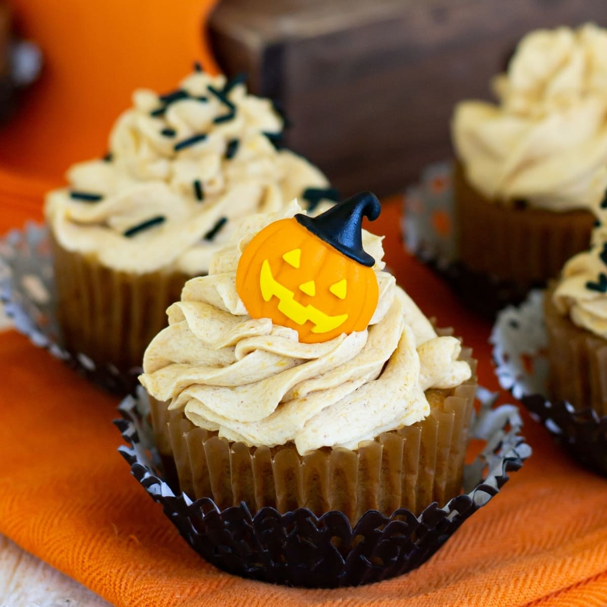 Pumpkin Cupcakes topped with Pumpkin Spice Buttercream Frosting and decorated for Halloween with candy pumpkins and sprinkles